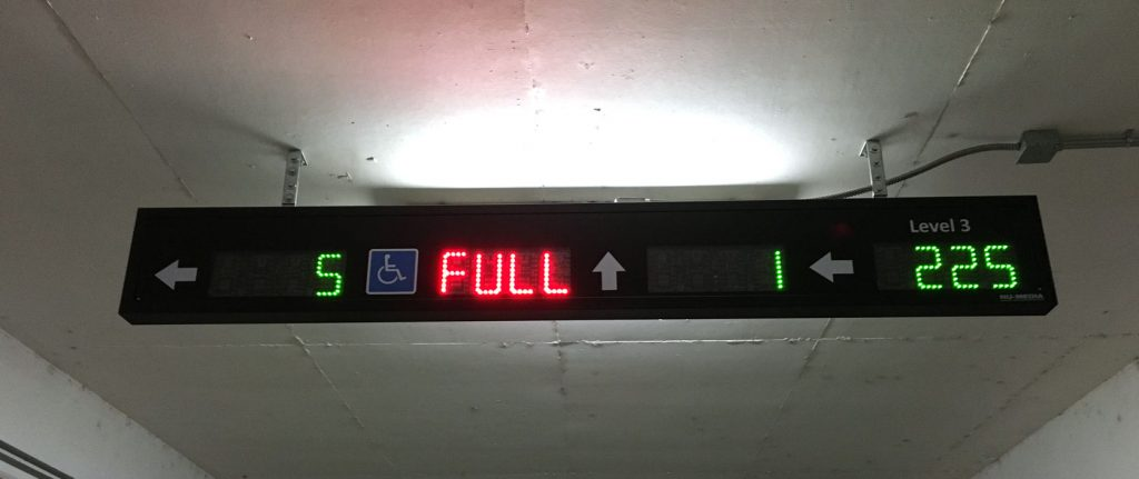 An automated parking guidance system display sign showing available spaces on each level