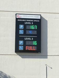 An automated parking guidance system sign on the exterior of the garage displaying available spaces by level