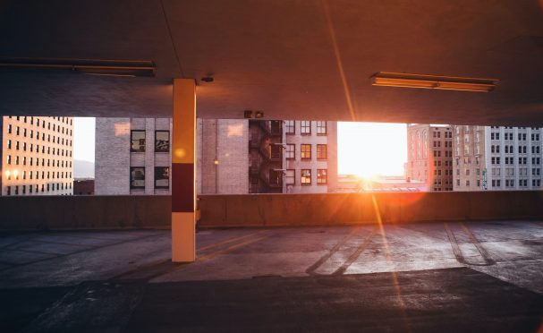 Empty parking garage with skyscrapers and sunset visible in background