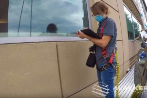 Restoration Consultant Erika Green makes notes on an iPad as she examines a building facade from a swing stage