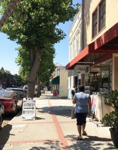 Streetscape in downtown Benicia with pedestrian, shops, and parked cars