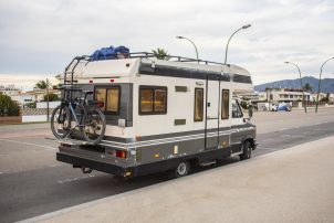 An inhabited recreational vehicle parallel parked on a street