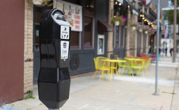 A parking meter for a curb space with sidewalk dining in the background