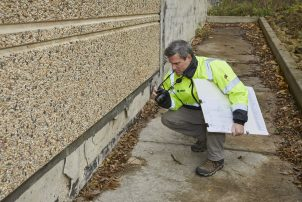 A Walker Consultants expert investigates damage to the exterior of a building