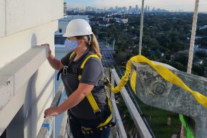 Kristen Navaid of Walker Consultants performs a building envelope investigation from suspended scaffolding