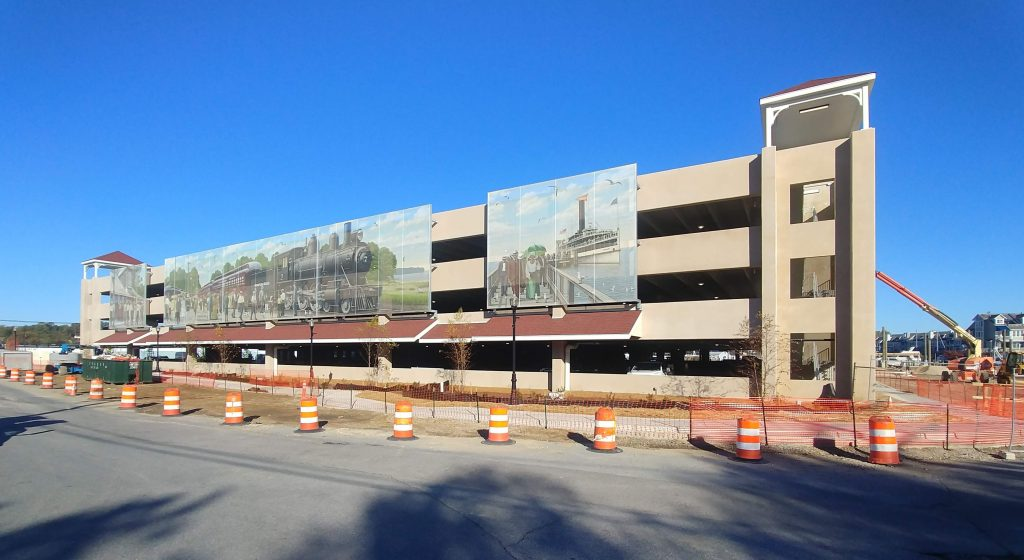 Exterior of parking structure under construction showing large murals attached to facade