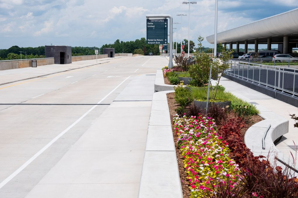 Elevated roadway at PTIA with sidewalk and landscape planters filled with colorful flowers