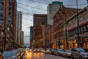 An inviting downtown street in the evening with lights strung above the road and lots of activity