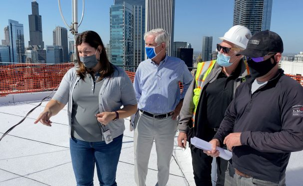 Sonia Surlej of Walker Consultants stands on the roof of a 54-story building and examines the progress of a roof replacement project with representatives from the manufacturer and contractor. Nearby skyscrapers and the Chicago skyline are visible in the background